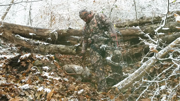 Hunter next to deer on forest floor